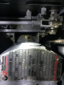 Reliance Motor viewed from top with mashed screw in background (middle or image, -ish)